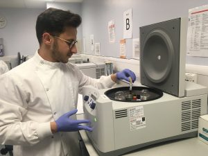 Clinical trial coordinator Arnold loading samples onto a centrifuge.