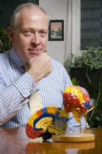 Image of Professor Charles Wolfe OBE at a desk with a model of a brain