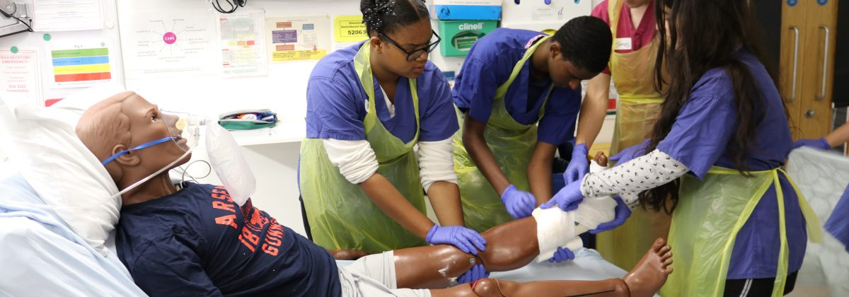 Students looking at a leg fracture on a practise dummy at Summer School