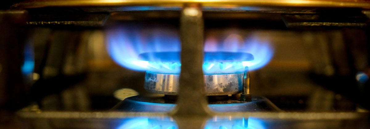 A close up of the flame on a gas cooker with a pan on top.