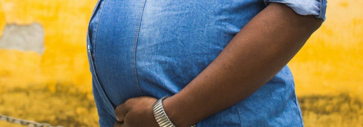 A pregnant woman in a denim shirt.