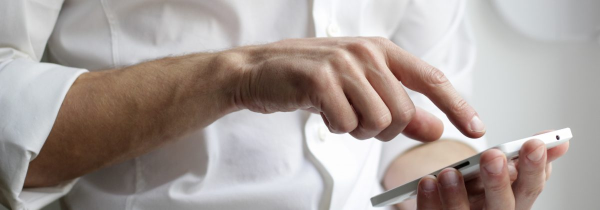 Person wearing a white sirt and typing on a smartphone
