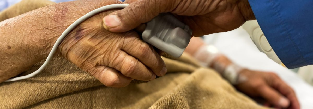 close up of person holding the hand of someone in hospital.